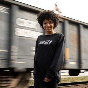 Junge Frau vor Güterzug