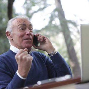 älterer Herr telefoniert am Laptop