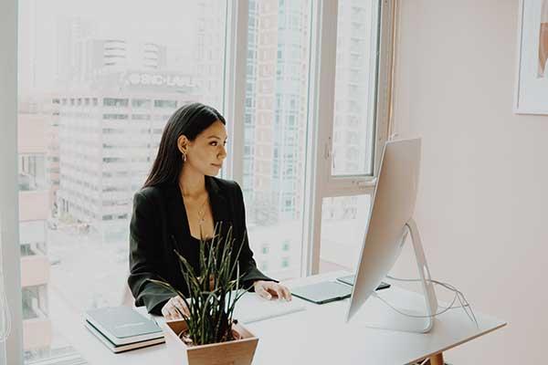 Eine Frau sitzt im Büro und arbeitet am PC