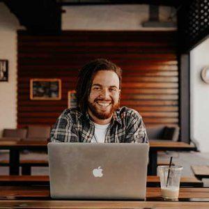 Mann sitzt lächelnd vor seinem Laptob und guckt dabei in die Kamera