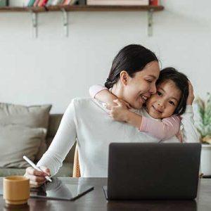 Mädchen umarmt ihre Mutter und sieht ihr beim arbeiten am Laptop zu